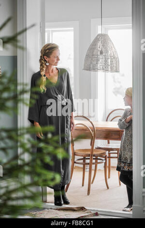 Sweden, Mother and daughter (6-7) standing in room with Christmas tree - Stock Photo