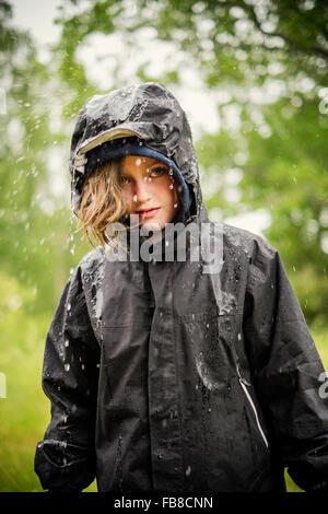 Sweden, Uppland, Blond girl (8-9) in raincoat - Stock Photo