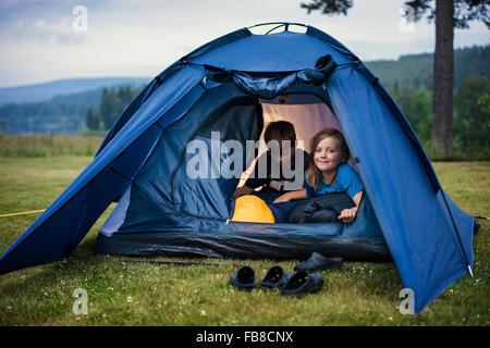 Sweden, Dalarna, Salen, Children (8-9, 10-11) in tent in meadow - Stock Photo