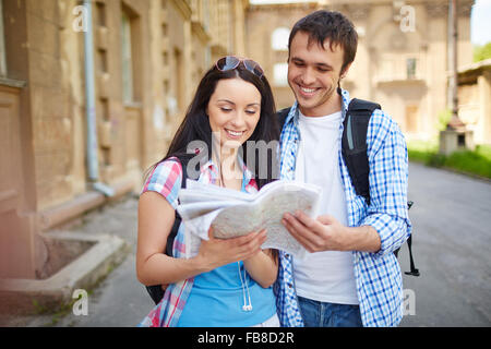 Happy couple of tourists on vacations searching a street in a map - Stock Photo