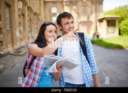 Couple of tourists in the city holding a map - Stock Photo