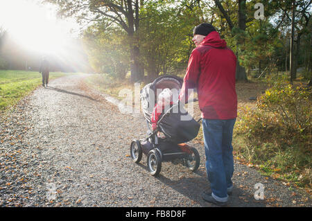 Sweden, Sodermanland, Nacka, man with son (12-17 months) walking in park - Stock Photo