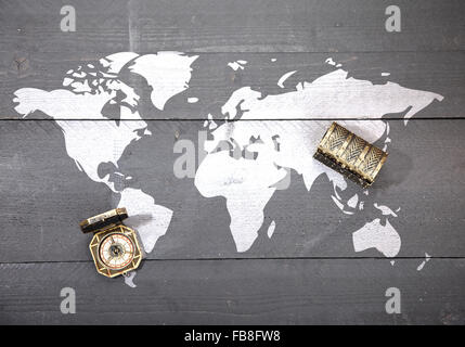World map with compass and treasure on dark black wooden background - Stock Photo