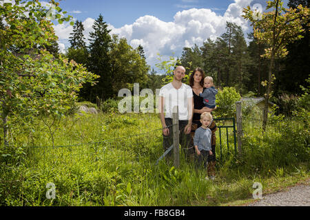 Sweden, Stockholm, Uppland, Nacka, Family with two children (18-23 months, 4-5) standing among lush foliage - Stock Photo