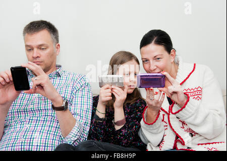 Girl (8-9) and parents texting on sofa - Stock Photo