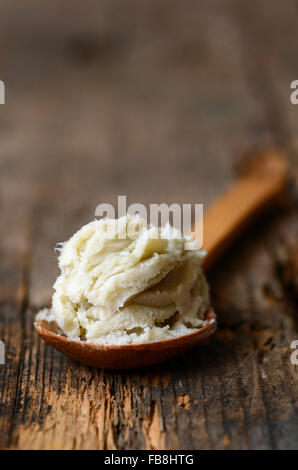 Unrefined raw shea butter on wooden background - Stock Photo