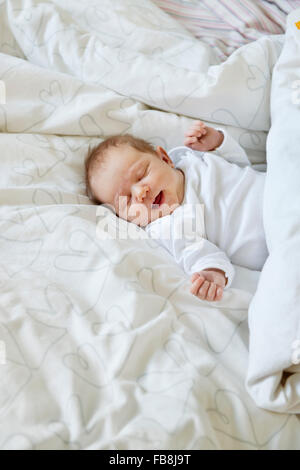Sweden, Newborn baby girl (0-1 months) lying in bed - Stock Photo