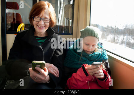 Sweden, Stockholm, Girl (10-11) with grandmother sitting in tram and using smart phones - Stock Photo