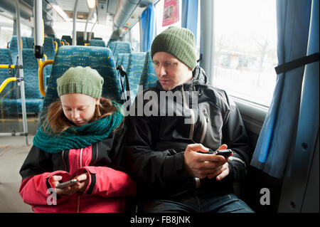 Sweden, Stockholm, Girl (10-11) with father sitting in tram and using smart phones - Stock Photo