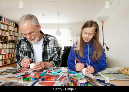 Sweden, Girl (10-11) with grandfather coloring eggs in living room - Stock Photo
