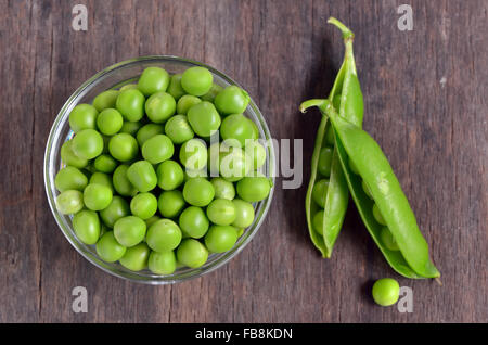 Close up of fresh peas on wooden table - Stock Photo