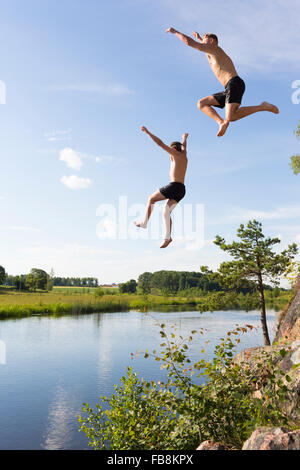 Sweden, Ostergotland, Mjolby, Young man and teenage boy (16-17) jumping into Svartan River - Stock Photo