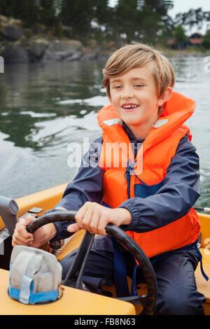 Sweden, Uppland, Runmaro, Barrskar, Boy (6-7) steering motorboat