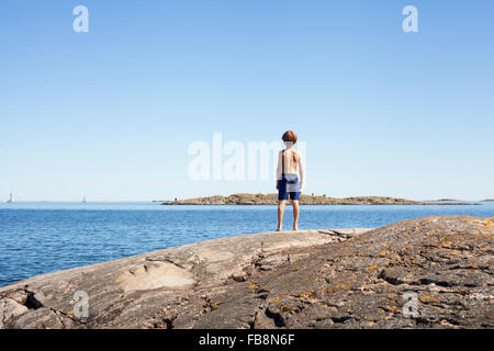Sweden, Uppland, Runmaro, Barrskar, Rear view of boy (6-7) looking at sea - Stock Photo