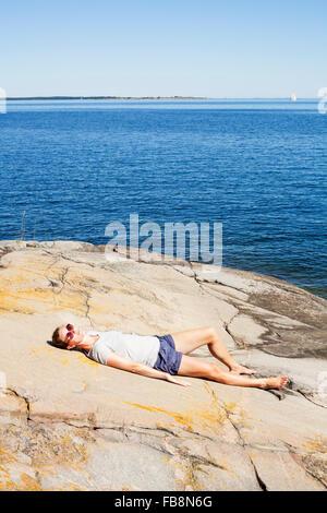 Sweden, Uppland, Runmaro, Barrskar, Woman relaxing by sea - Stock Photo