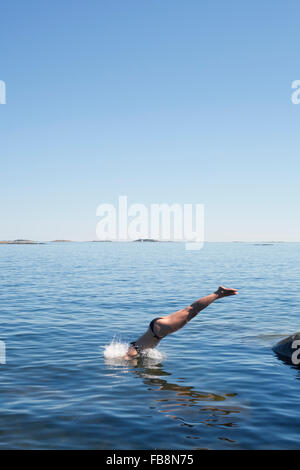 Sweden, Uppland, Runmaro, Barrskar, Woman jumping into sea - Stock Photo
