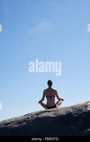 Sweden, Uppland, Runmaro, Barrskar, Rear view of woman practicing yoga on rock - Stock Photo
