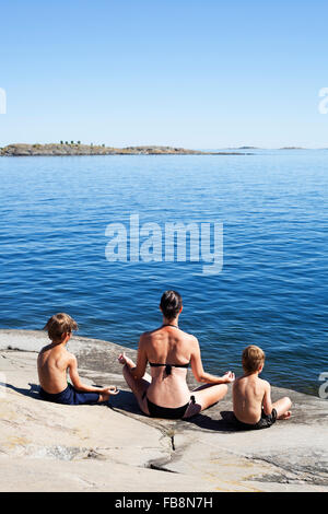 Sweden, Uppland, Runmaro, Barrskar, Rear view of mother and sons practicing yoga on seaside - Stock Photo