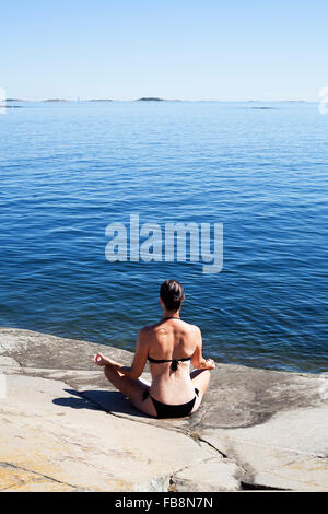 Sweden, Uppland, Runmaro, Barrskar, Rear view of woman practicing yoga on seaside - Stock Photo