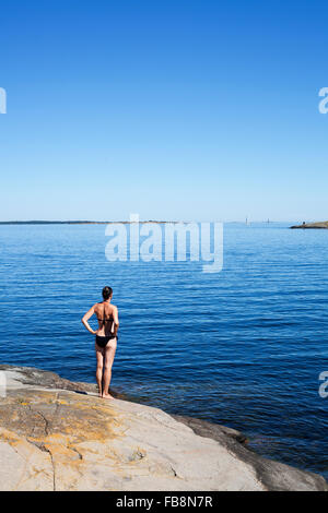 Sweden, Uppland, Runmaro, Barrskar, Woman standing on seaside and looking at view - Stock Photo