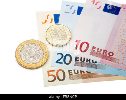 Pound coins and Euros isolated on a white background. - Stock Photo