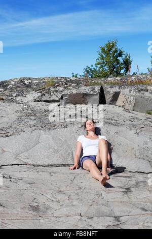 Sweden, Uppland, Runmaro, Barrskar, Woman relaxing on rock - Stock Photo