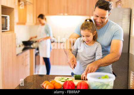 father teaching little daughter cutting vegetables while mother cooking on background - Stock Photo