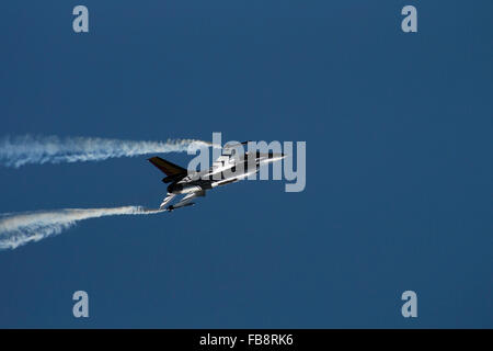 Fighter jet aeroplane with missiles against dark blue sky with white smoke at air show. International Air Tattoo - Stock Photo