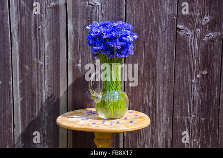 Sunlit blue cornflowers in a jug placed by the rustic old wooden wall outdoors - Stock Photo