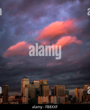 London, UK. 12th January, 2016. UK Weather: Pink cloud evening sunset over Canary Wharf business park buildings - Stock Photo