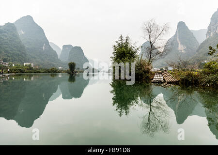 Yulong River, Yangshuo - China. January 2016 - People traveling along the Yulong river on traditional bamboo rafts. - Stock Photo