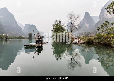 Yulong River, Yangshuo - China. January 2016 - People traveling along the Yulong river on top of traditional bamboo - Stock Photo