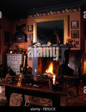 Mirror above fireplace in a dark Victorian style living room with a crofter's style wooden chair - Stock Photo