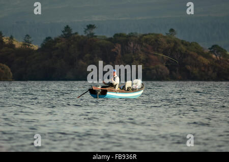 Lone angler fisherman fly fishing from boat - Stock Photo