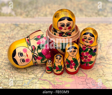 A wooden matryoshka doll, also known as a Russian nesting doll, on a map of Russia - Stock Photo