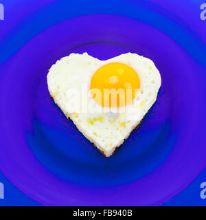 Heart shaped egg on blue dish - Stock Photo