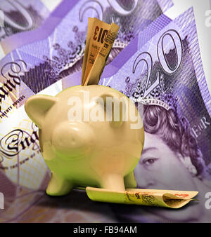 Cream coloured ceramic piggy bank with ten pound notes and a background of twenty pound notes - Stock Photo