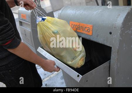 man taking out trash in malaga central - Stock Photo