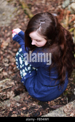 Back of a young woman with long brown wavy hair sitting on a step waiting - Stock Photo