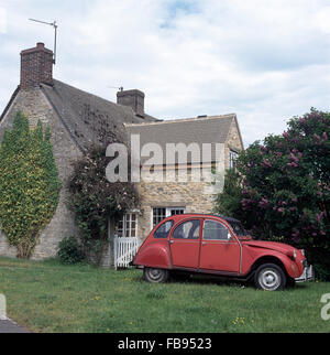 Vintage red Citroen 2CV on grass beside stone country cottage with a well built extension - Stock Photo