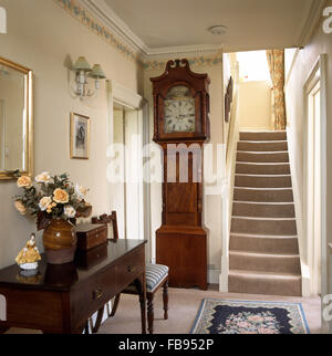 Antique long case clock in country hall with an antique console table - Stock Photo