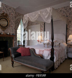 Grey chaise longue at the foot of a four poster bed with white lace drapes and a breakfast tray - Stock Photo