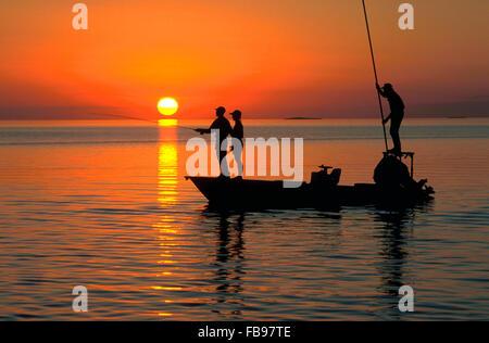 A couple enjoys flyfishing at sunset on Florida Bay from a backcountry flats fishing boat at Islamorada, a village - Stock Photo