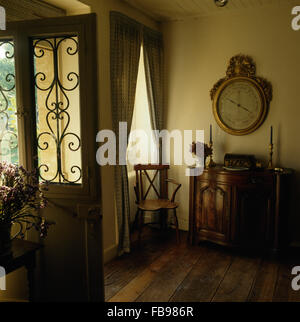Large antique barometer above antique cupboard in traditional hall with wooden flooring and a half glazed door with - Stock Photo