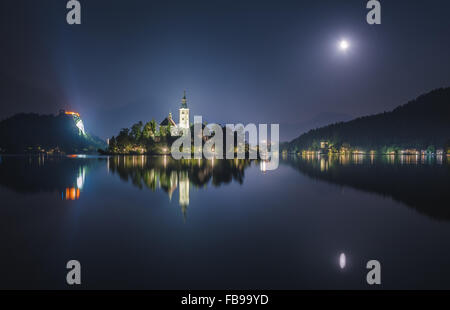 Illuminated Catholic Church on a Little Island and Bled Castle on Bled Lake in Slovenia at Night Reflected on Water - Stock Photo