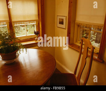 Cream blind on windows in eighties dining room with circular table - Stock Photo
