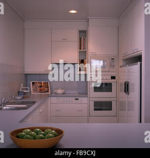 White Double Oven And An American Style Fridge In A White Nineties Kitchen    Stock Photo