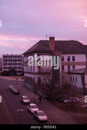 Run down building in the former East Germany, lit by dramatic pink sky - Stock Photo