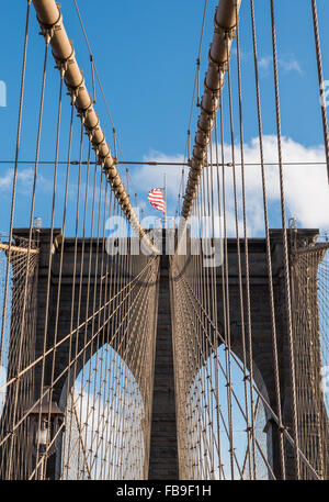 Looking upwards towards one of the towers of Brooklyn Bridge with granite and limestone brickwork and suspension - Stock Photo