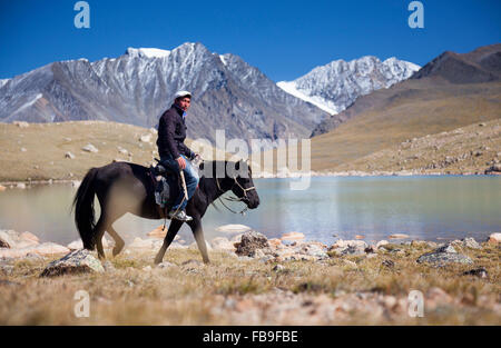 Tsaganaa, a guide and herder riding near a glacial lake in the remote Kharkhiraa Turgen National Park, Mongolia. - Stock Photo